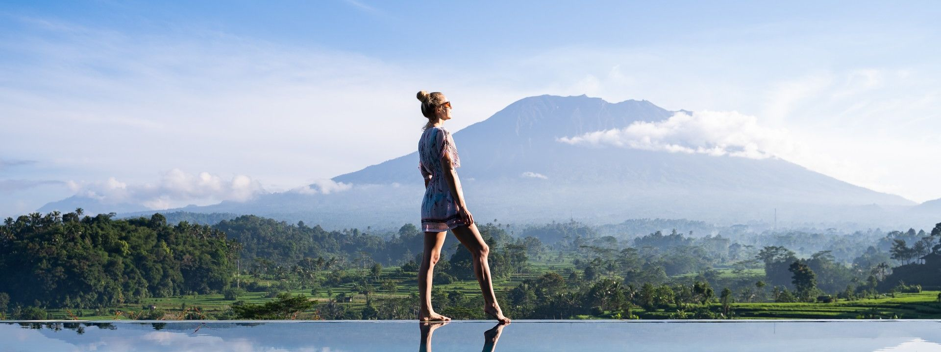 Woman on the pool in front of volcano